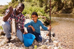 Portrait of fishermen - African man and his little son posing with bucket of fish catch
