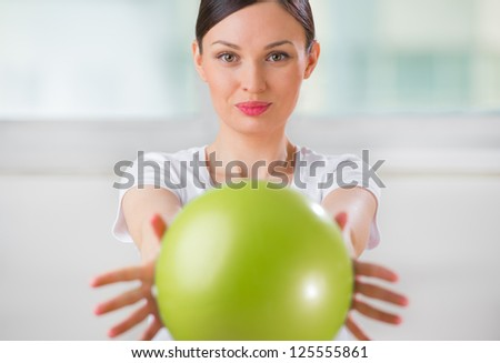 Portrait of fit and healthy woman with toning ball at fitness club or at home positive and happy doing exercises