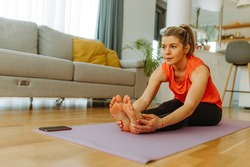 Portrait of fit blonde woman in sportswear standing on mat while performing seated forward bend yoga pose. Young woman is exercising yoga at home. Self isolation due to COVID19 pandemic.