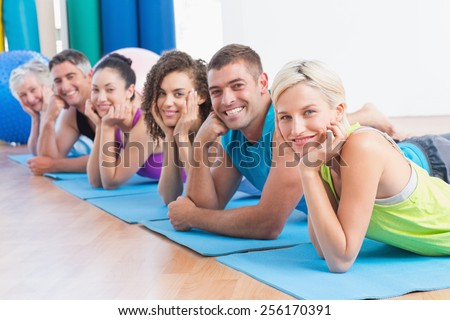 Portrait of fit people relaxing on exercise mats at fitness studio