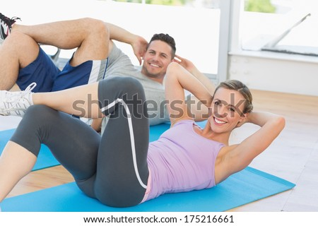 Portrait of fit woman and man doing sits up in fitness studio