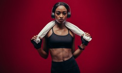 Portrait of fit young african woman with headphones and towel on red background. Female relaxing after workout.