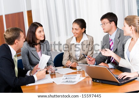 Portrait of five businesspeople sitting at the table and discussing important questions in the office