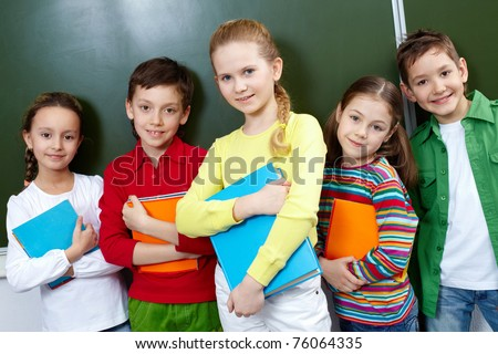 Portrait of five pupils looking at camera in classroom