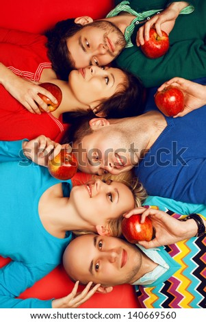 Portrait of five stylish close friends hugging and lying over red background. Guys having fun and holding red apples. Healthy food concept. Hipster style. Studio shot