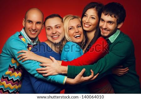 Portrait of five stylish close friends hugging and posing over red background. Guys having fun. Shiny smile and healthy white teeth. Hipster style. Studio shot