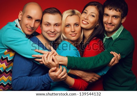 Portrait of five stylish close friends hugging, smiling and posing over red background. Guys having fun. Hipster style. Studio shot