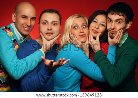 Portrait of five stylish close friends hugging, smiling and posing over red background. Guys having fun and holding cheeks of their neighbor. Hipster style. Studio shot