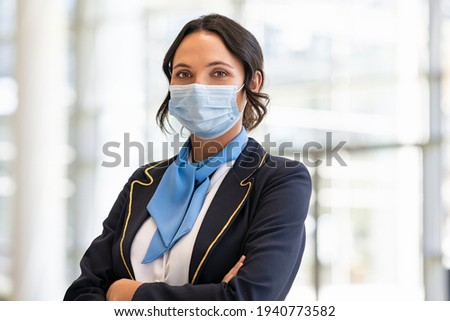 Portrait of flight attendant standing at airport terminal wearing face mask for safety against covid-19. Stewardess with surgical mask looking at camera, aircrafts are waiting and preparing flight. Photo stock ©