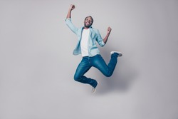 Portrait of flying, crazy, carefree, free, cheerful, funny man in sneakers, denim outfit, jumping with raised arms, celebrating victory, having fun, rest, relax, leisure, isolated on grey background