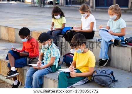 Portrait of focused diligent schoolchildren in face masks during lesson outside school in warm autumn day. New lifestyle in coronavirus pandemic Photo stock ©