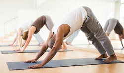 Portrait of focused man making yoga exercises with friends at fitness center