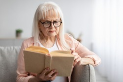 Portrait of focused mature woman trying to read paper book, squinting to see more clearly, wearing glasses, having difficulties seeing text because of vision problems, free copy space