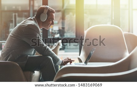 Portrait of focused middle-aged businessman in headphones listening to audio business course at work. E-learning and online professional education concept. Horizontal shot. Side view