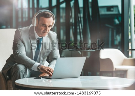 Portrait of focused middle-aged businessman in headphones listening to audio business course at work. E-learning and online professional education concept. Horizontal shot