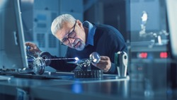 Portrait of Focused Middle Aged Engineer in Glasses Working with High Precision Laser Equipment, Using Lenses and Testing Optics for Accuracy Required Electronics