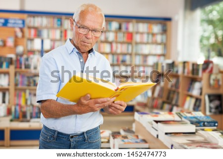 Portrait of  focused older man looking inside of books while visiting bookstore