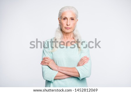 Portrait of focused retiree with crossed arms looking wearing turquoise sweater isolated over white background