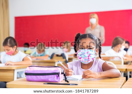 Portrait of focused schoolgirl wearing protective face mask working at lesson in classroom, writing exercise