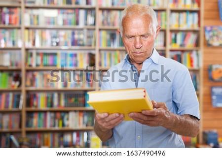 Portrait of focused senior man choosing book at shelves in bookshop