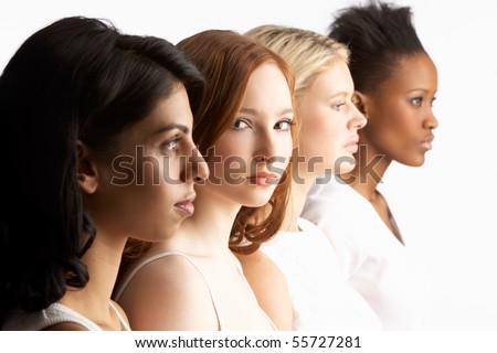 Portrait Of Four Attractive Young Women In Studio Standing In Line