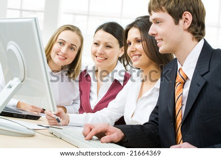 Portrait of four businesspeople discussing computer work