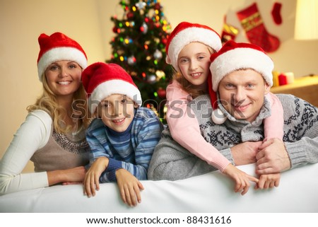 Portrait of four happy family members in Santa caps looking at camera with smiles