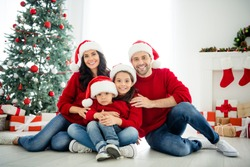 Portrait of four nice attractive idyllic affectionate cheerful big full adopted foster family celebrating newyear enjoying winter december vacation weekend in light white interior living-room