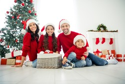 Portrait of four nice attractive lovely cheerful dreamy friendly big full foster family spending celebrating newyear sitting on floor enjoying leisure in light white interior room indoors