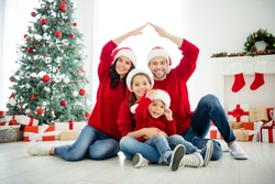 Portrait of four nice attractive lovely sweet idyllic affectionate cheerful big full careful family brother sister celebrating newyear leisure showing roof in light white interior living-room