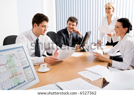 Portrait of four professionals sitting at the table and discussing a business idea in the office