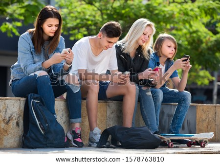 Portrait of four smiling russian  teenagers sitting with their mobile phones outdoors in town Сток-фото ©