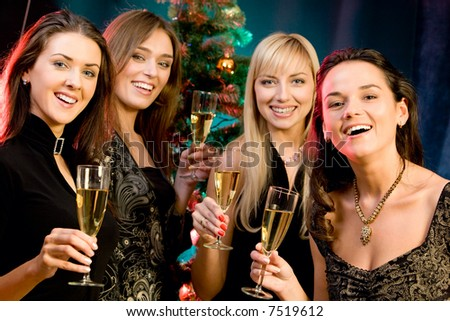 Portrait of four woman holding the glasses of champagne on the background of christmas-tree
