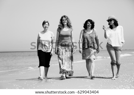 Portrait of four  40 years old women walking on seaside