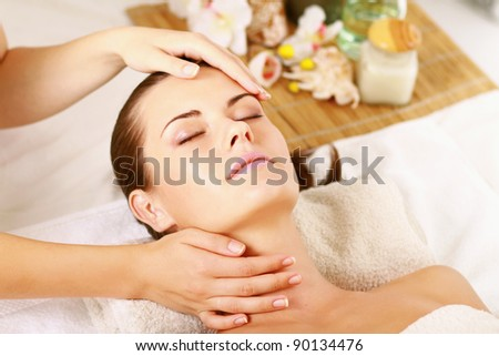 Portrait of fresh and beautiful brunette woman taking head massage , isolated on white background