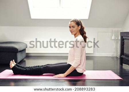 Portrait of fresh young woman sitting on exercise mat looking at camera smiling. Beautiful female exercising in living room.