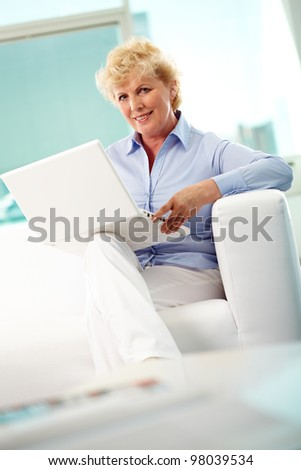 Portrait of friendly aged woman typing and looking at camera