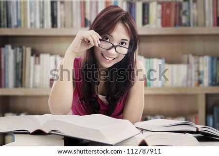 Portrait of friendly asian female college student looking at someone in the library