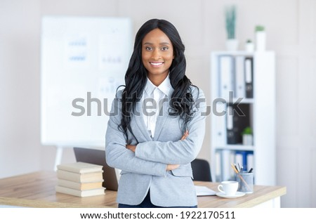 Portrait of friendly black female manager in formal suit standing with crossed arms at contemporary office. Successful African American busineswoman posing and smiling at camera