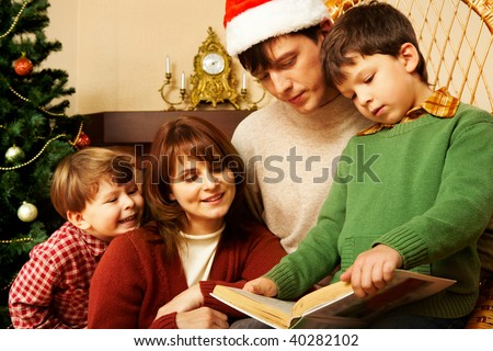 Portrait of friendly family looking into interesting book on Christmas day