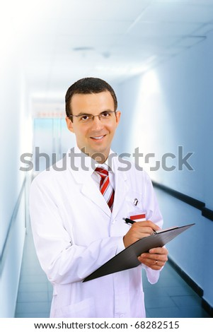 Portrait of friendly medical doctor in hospital  with medical pad.