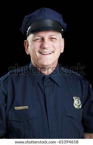 Portrait of friendly, smiling police officer on black background. - stock photo