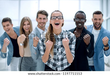 Portrait of friendly team of employees rejoicing in the office