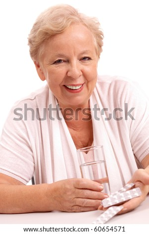 Portrait of friendly woman with glass of water and tablets looking at camera
