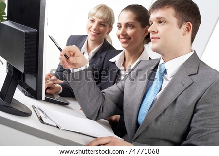 Portrait of friendly workteam looking at while confident businessman pointing at screen