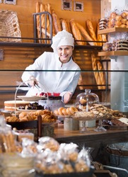 Portrait of friendly young woman at bakery display with pastry