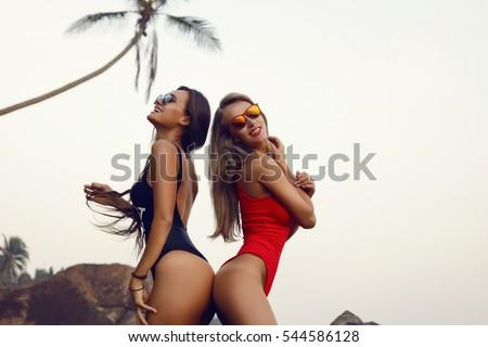 Portrait of friends beautiful happy women,sea and spraying at the beach on beautiful summer sunset light.girls playing