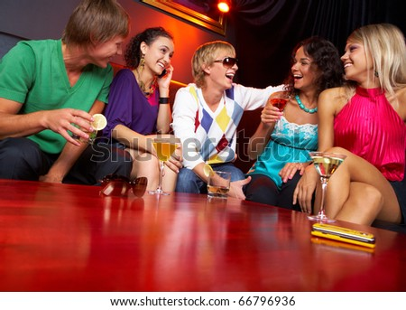 Portrait of friends sitting on the sofa and chatting in the nightclub