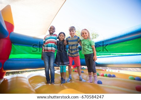 Portrait of friends with arms around standing on bouncy castle at playground