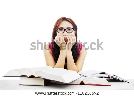 Portrait of frightened female college student with textbooks biting her nails - stock photo